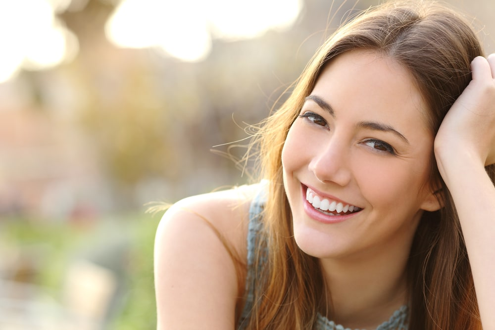 Woman smiling with perfect smile and white teeth in a park