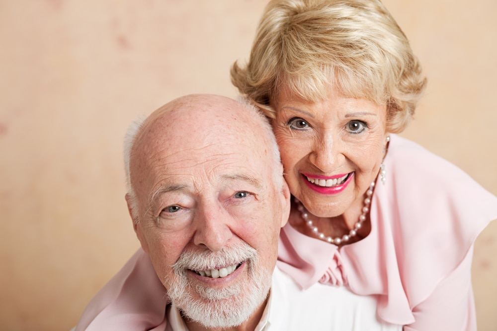Two smiling mature with implant dentures